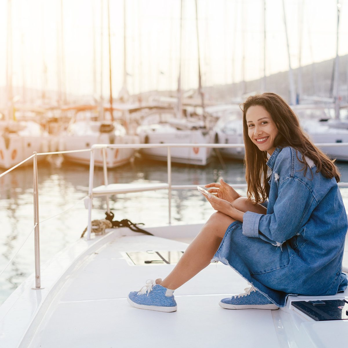 Beautiful young girl sits on the deck of a yacht and looks into a smartphone