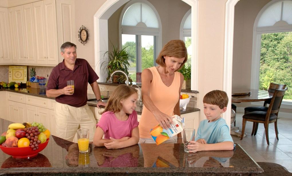 Imagem mostra uma família reunida bebendo suco de laranja.