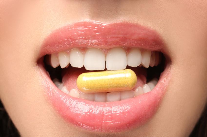 Imagem de uma mulher com uma cápsula na boca.