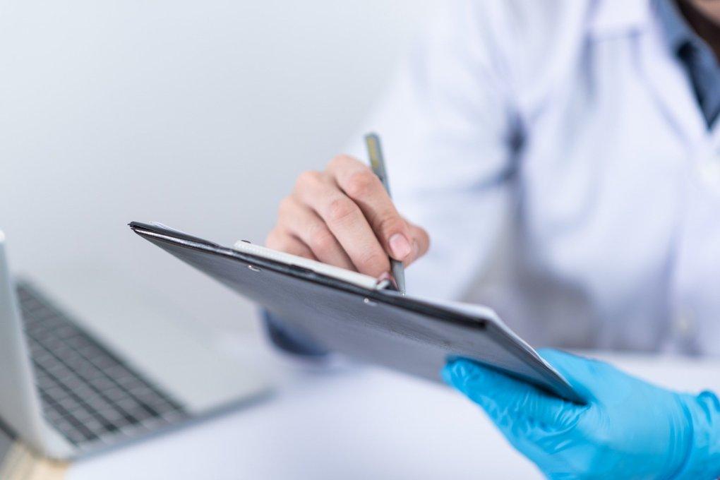 Médico fazendo anotações na prancheta.