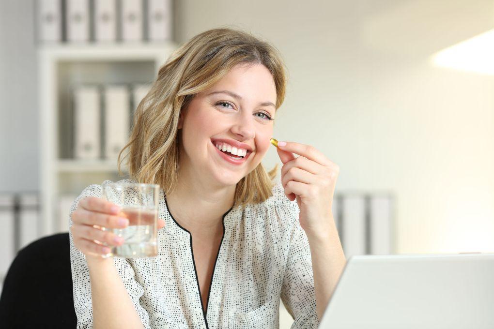 Imagem de uma mulher tomando um comprimido.