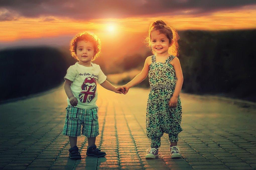 Menino e menina de mãos dadas com por do sol atrás.