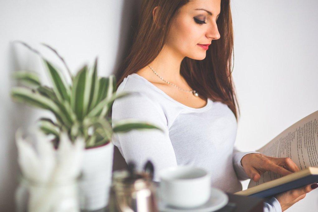 Imagem mostra uma mulher lendo um livro.