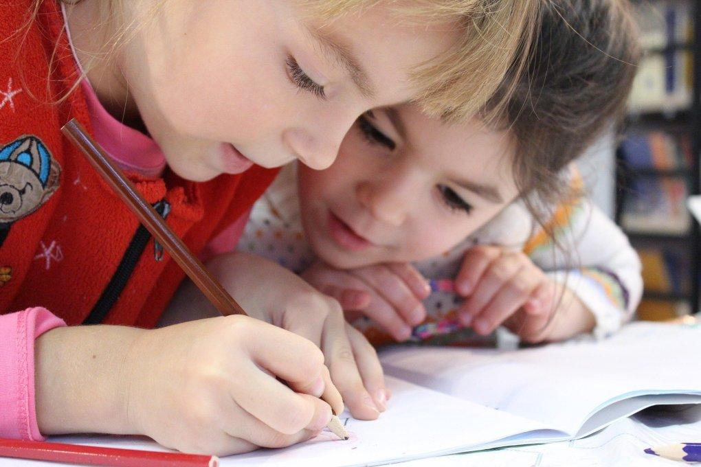 Imagem mostra duas crianças atentas em um livro.