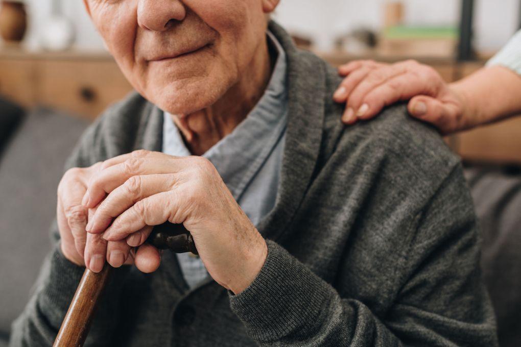 visão recortada de um aposentado feliz com as mãos da esposa no ombro