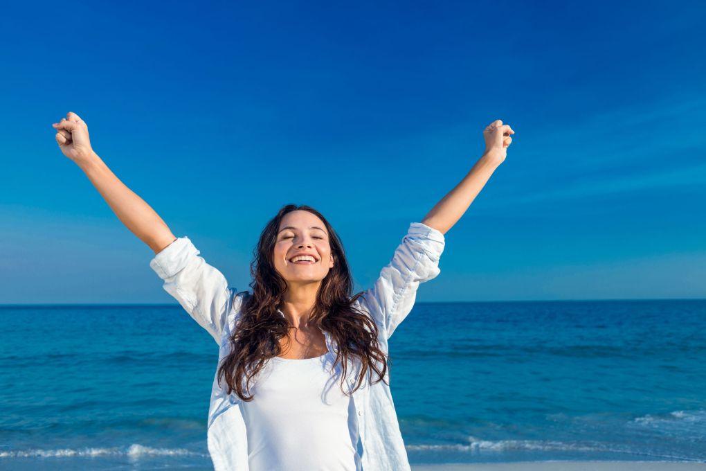 Donna felice che sorride alla spiaggia in una giornata di sole