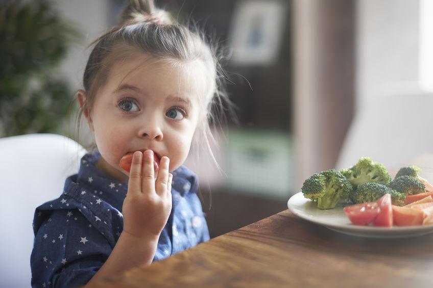 little girl eating some strawberries