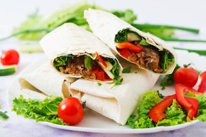 Burritos wraps with minced sunflower protein and vegetables on a light background.