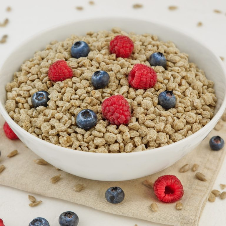 Organic vanilla high protein cereal in a white bowl topped with raspberries and blueberries.