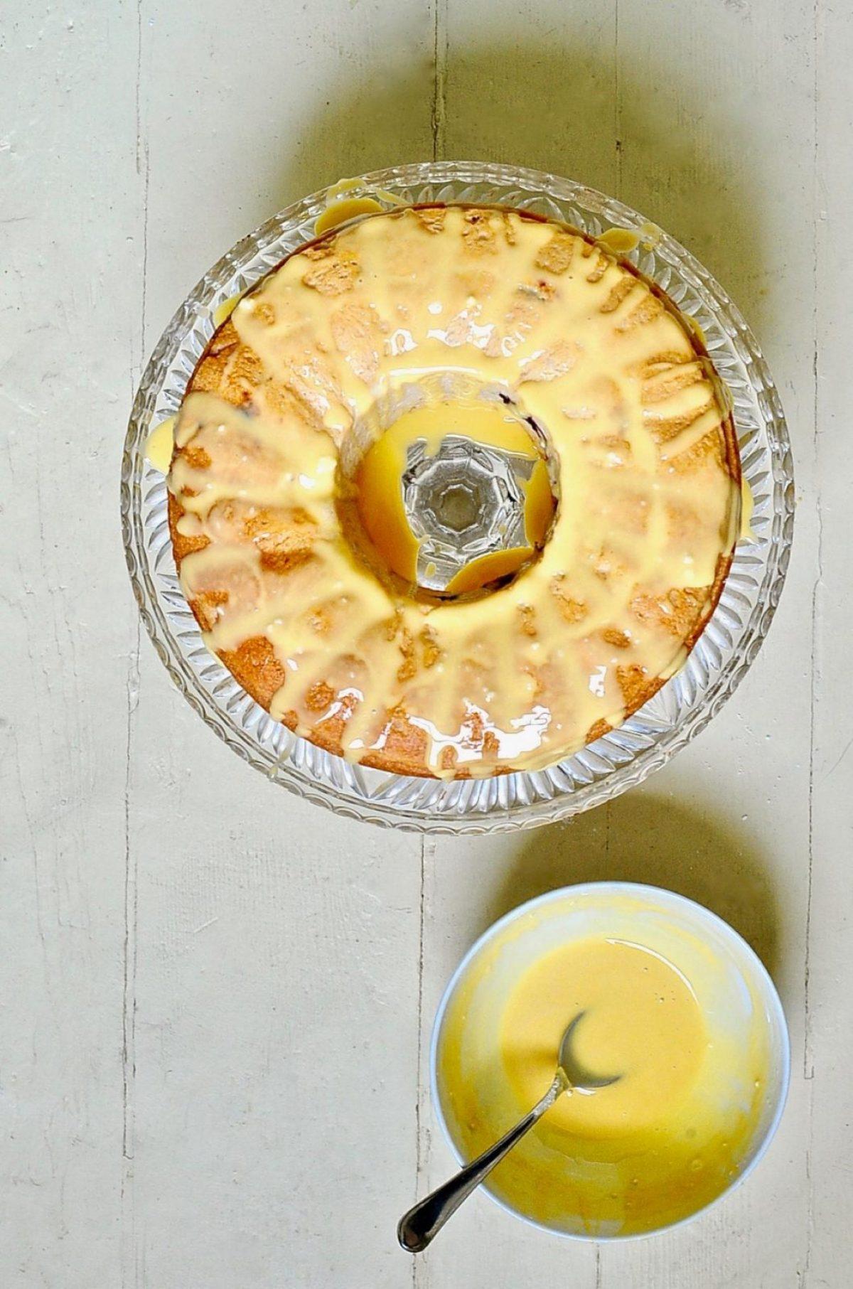 Classic vegan Babka with orange glaze on a glass cake stand.