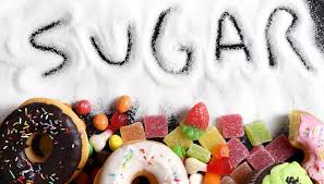 The word sugar drawn in spilled sugar and sweets below the word