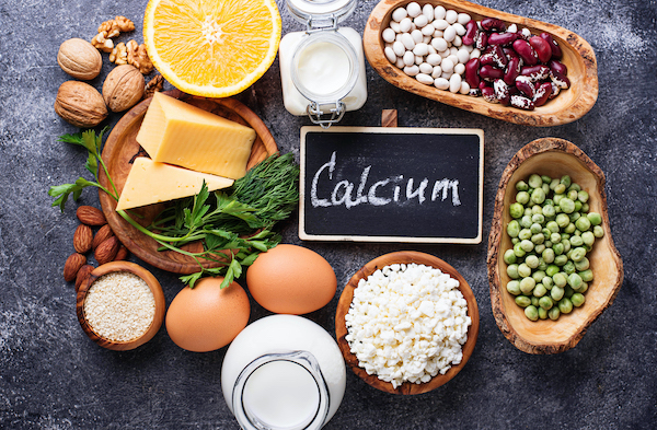 calcium rich foods for breastfeeding like milk eggs and beans on a table