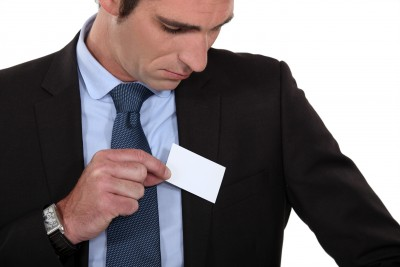 Man putting business card in pocket networking