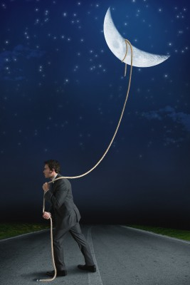 Business man chasing catching moon success goals