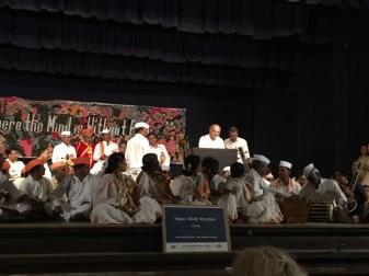 Kongressin järjestävä Ganesh Devy puhuu kutsuvieraille paikallisten muusikoiden ympäröimänä.
