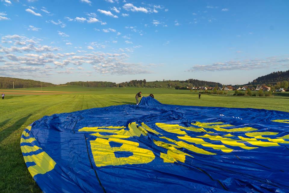 Die zwei Männer hinten rechts und links sollen den Ballon während des Aufblasens und Aufheizens an langen Seilen festhalten.