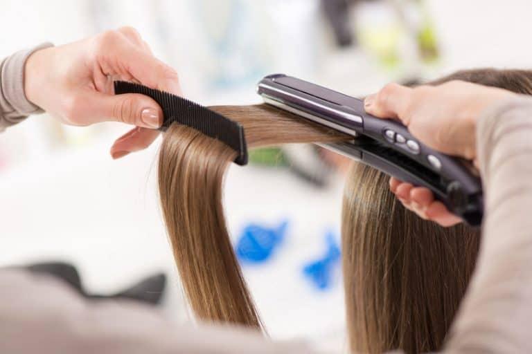 Parrucchiera che piastra i capelli
