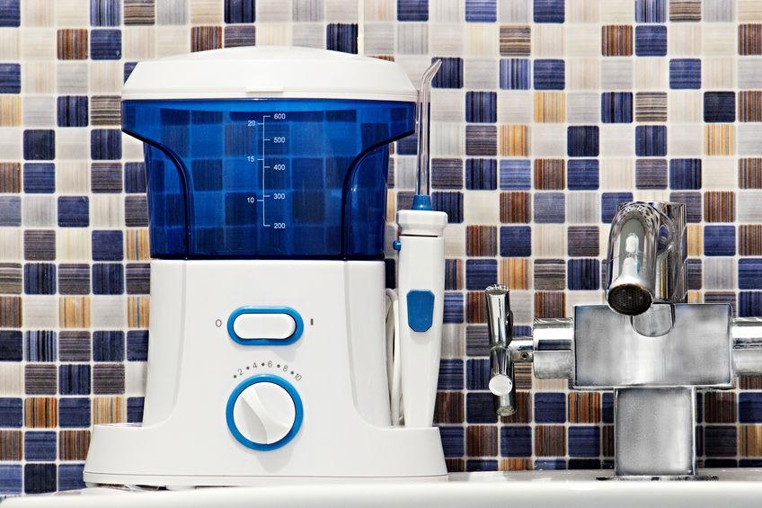 Igiene orale, concetto di oggetti da bagno. Denti della bocca che puliscono strumento moderno dell'irrigatore sul lavandino.