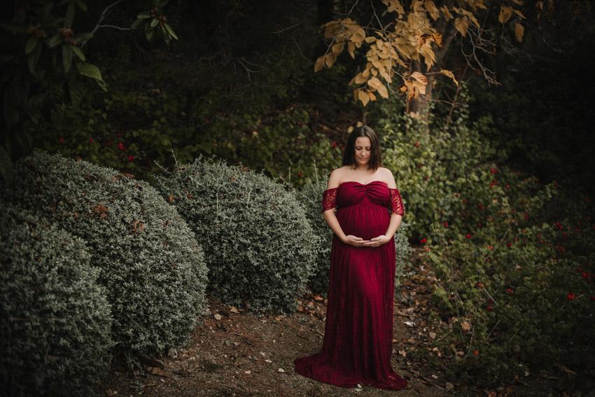 mujer embarazada vestida de rojo posando en el parque