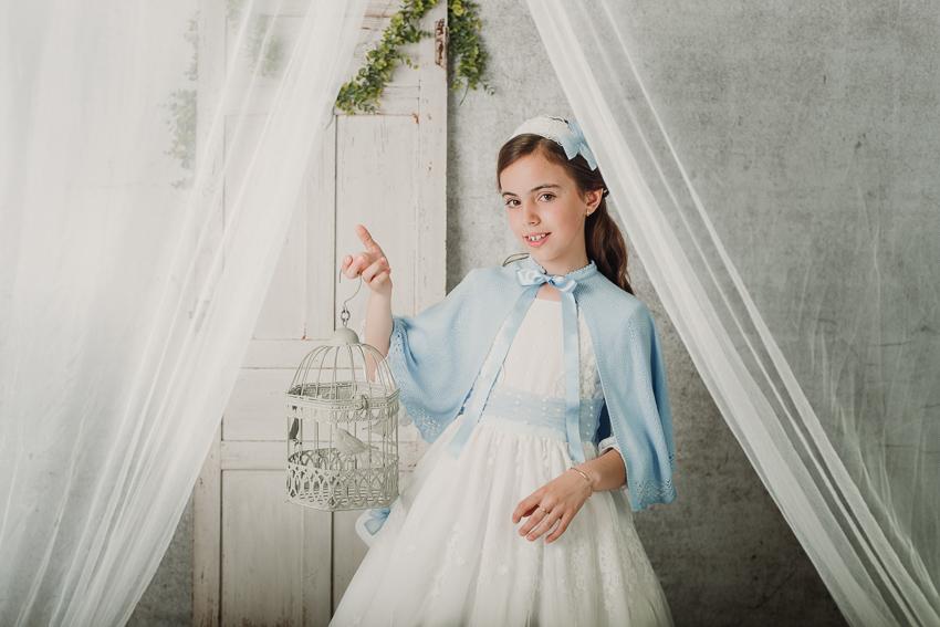 retrato de niña de comunión en estudio sujetando una jaula con la mano