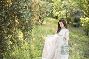 niña con jaula en una mano y cogiendose el vestido con la otra