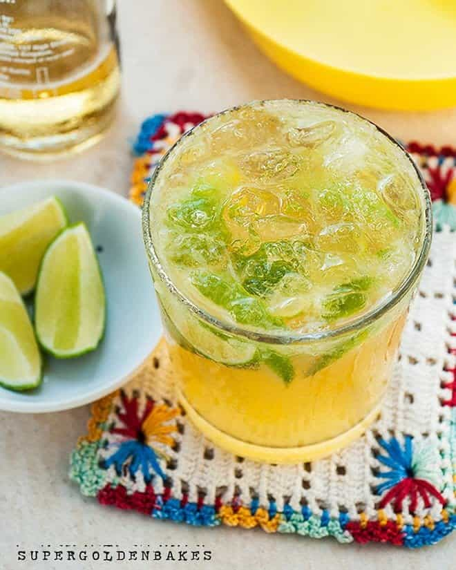 Beergarita cocktail topped with ice in a glass with lime wedges on the side