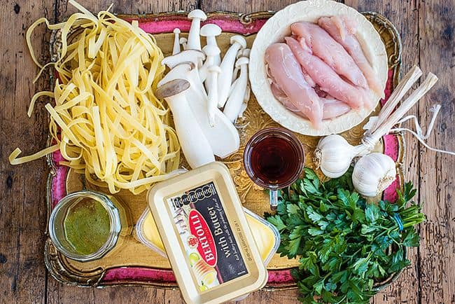 Ingredients for pasta with chicken and mushrooms arranged on a rustic tray