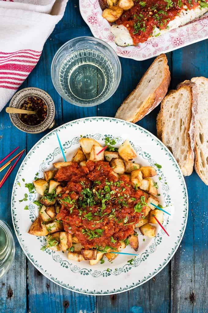 Summery Spanish oven-baked patatas bravas with seas bass. The potatoes make a great starter to share or turn them into a main with the fish.