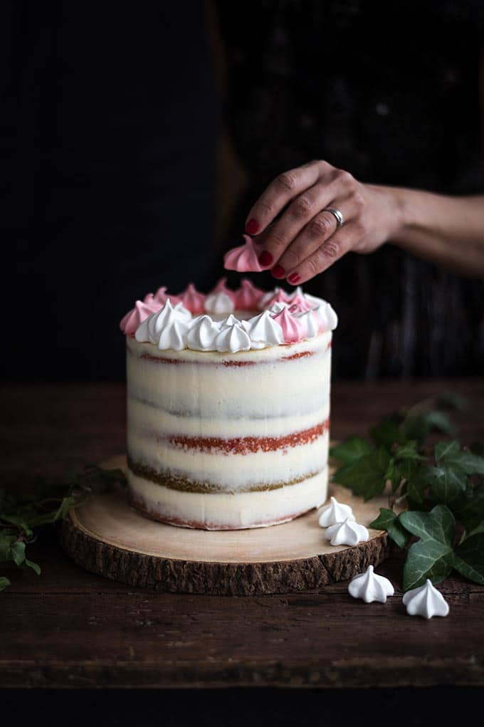 A showstopping Christmas layer cake filled with cranberry compote, whipped mascarpone frosting and crowned with a sweet meringue wreath. Slice to reveal the festive red and green layers! #christmascake #layercake #christmas