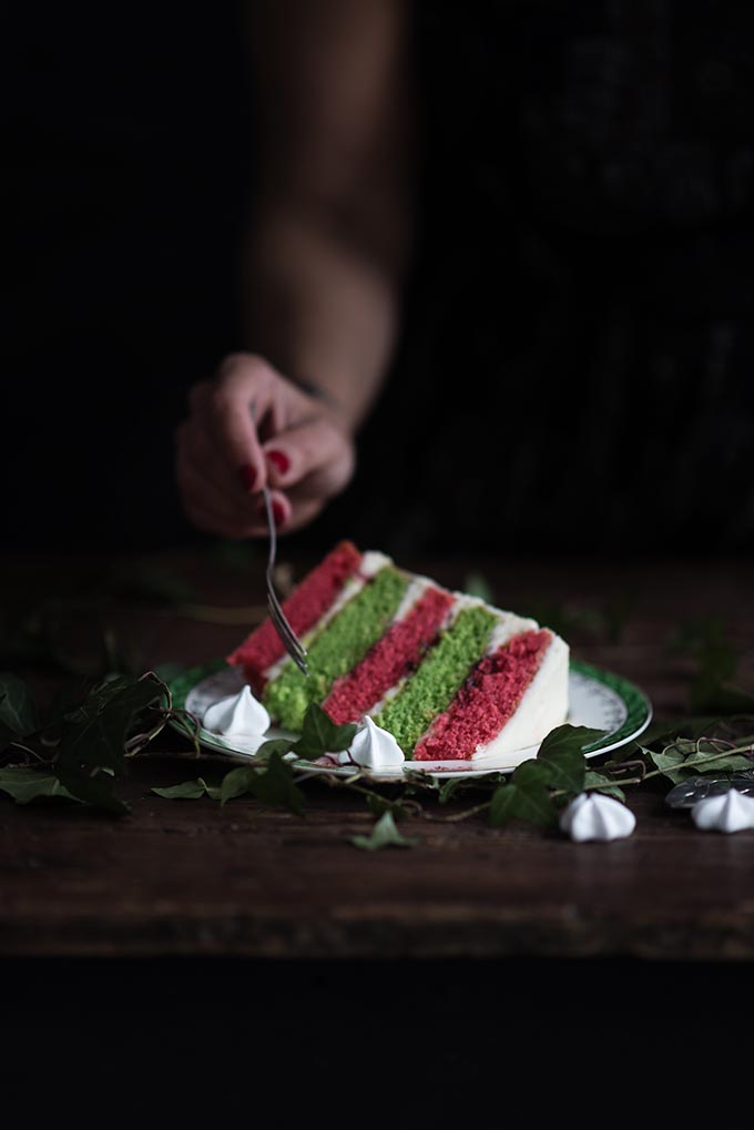 A showstopping Christmas layer cake filled with cranberry compote, whipped mascarpone frosting and crowned with a sweet meringue wreath. Slice to reveal the festive red and green layers! #Christmas #layercake #festivecake #rainbowcake