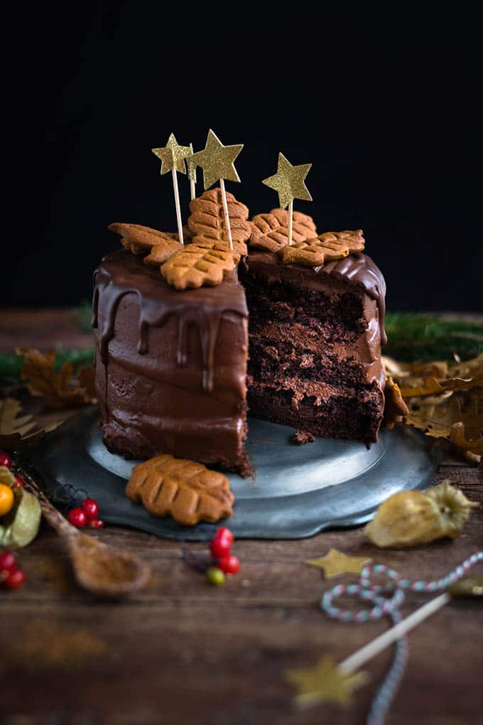 Vegan chocolate and gingerbread layer cake with gingerbread cookie decorations. Perfect for Christmas or birthdays and celebrations.