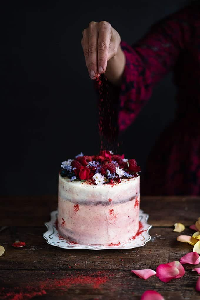 Red velvet layer cake decorated with flowers and berries