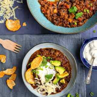 Bowl of lentil and bean chili topped with sour cream, avocados, grated cheese and Popchips