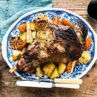 Roast leg of lamb on a bed of roast vegetables