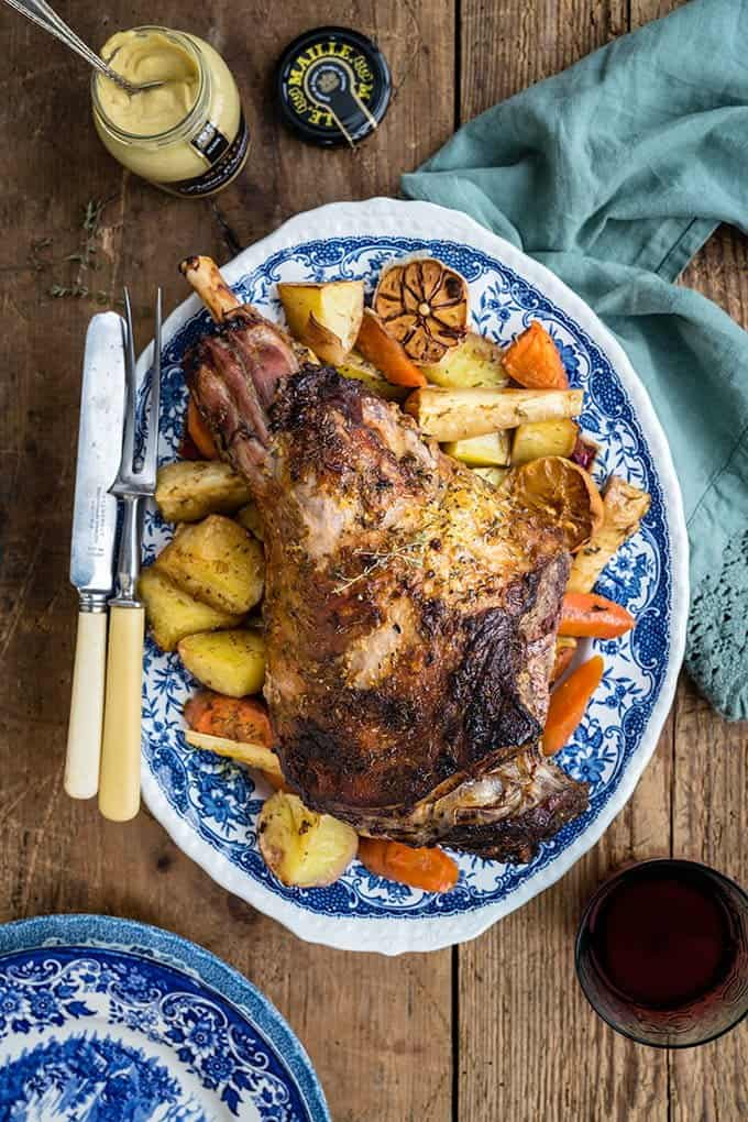 Roast leg of lamb on a bed of roast vegetables arranged on blue patterned platter
