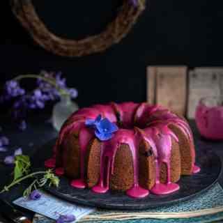 Blueberry bundt cake with blueberry glaze on a black marble platter