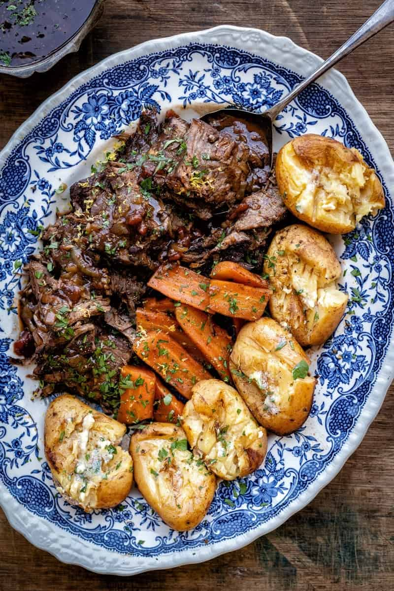 Close up of sliced balsamic beef brisket arranged on a blue platter with potatoes and carrots