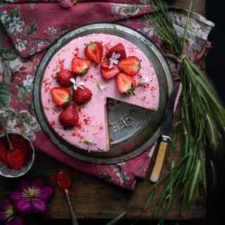 Sliced strawberry cheesecake on a vintage pie plate