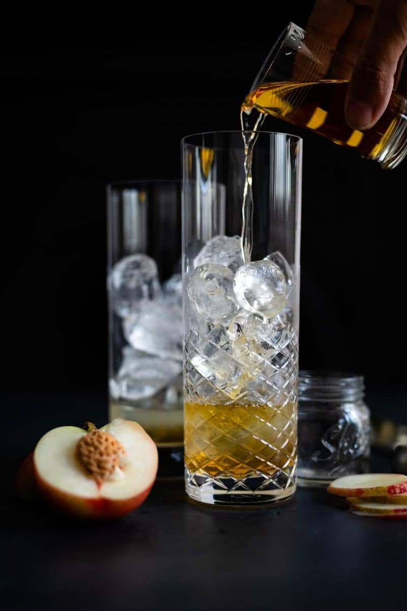 Adding whisky to a tall glass filled with ice