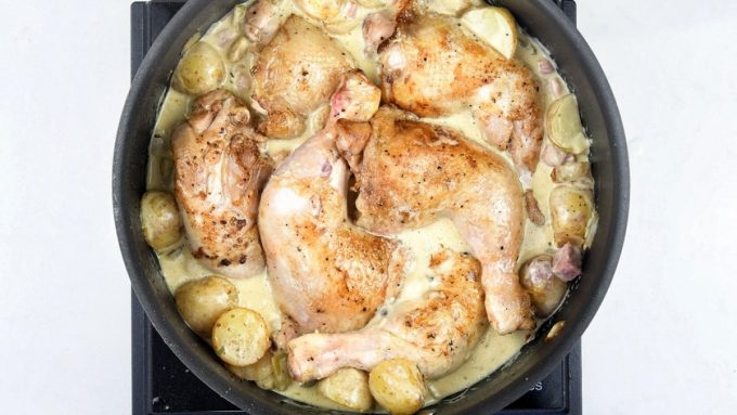 Chicken legs nestled among potatoes and cream in a large pan