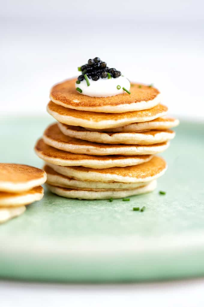 Stack of blini pancakes topped with sour cream and caviar