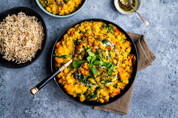 Vegan dal with red lentils, squash, chickpeas and spinach in a bowl with rice on the side