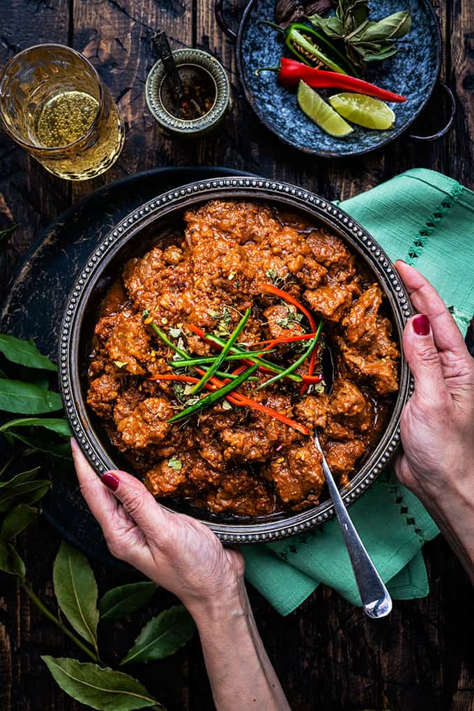 Overhead image of large bowl of lamb curry on a rustic wood table