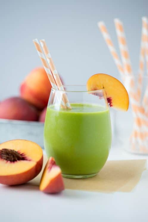peachy green smoothie in a glass with straws