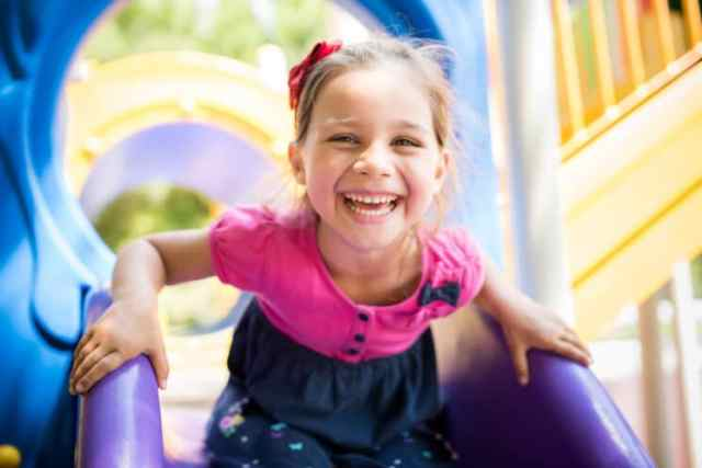 happy girl playing on the slide