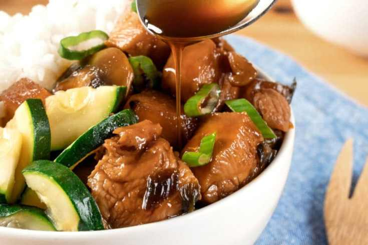 drizzling marinade on chicken teriyaki with veggies