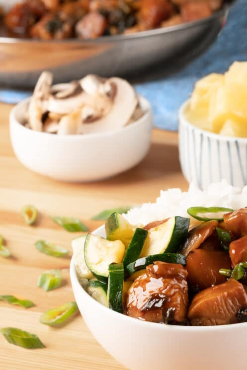 chicken teriyaki with mushrooms and pineapple in bowls