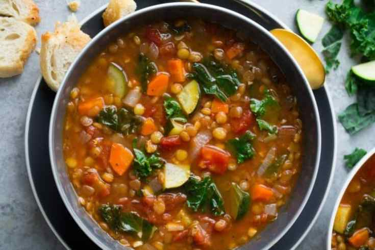 colorful lentil soup with veggies in a bowl with bread on the side