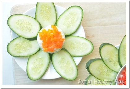Sliced Cucumbers shaped like a flower with dip in the middle.