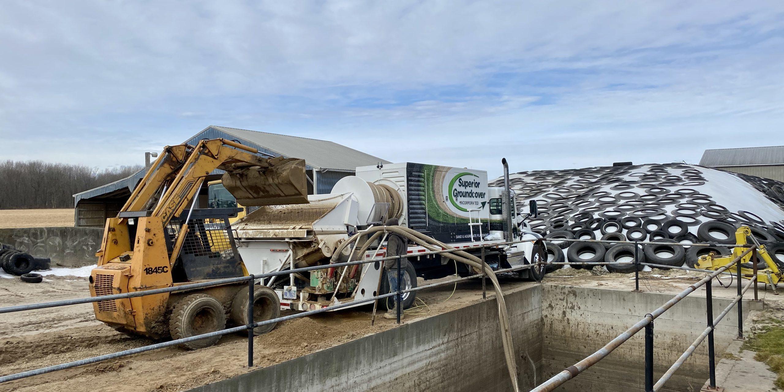 Stone blower truck installing peastone for a dairy farm in Michigan